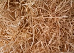 Decorative packing material, natural wooden shredded wood shavings for gifting, shipping and stuffing. Top view, macro straw