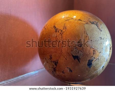 Decorative papier-mâché globe on red wooden bookshelf Foto d'archivio ©