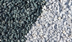 Decorative pebbles used in the garden or yard. Half are white and half greenish gray. Background and texture