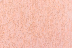 Decorative plaster and pink paint on the walls.Rough, uneven surface. Vintage background and texture. Pastel, light tone.