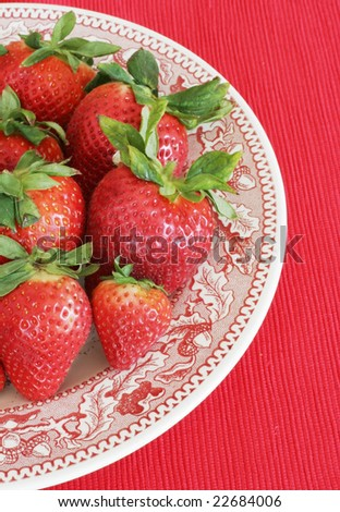 decorative plate with fresh strawberries and red background