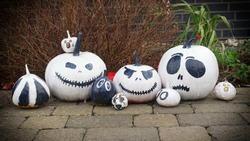 Decorative pumpkins of different sizes in black and white are arranged in a row in front of the house. Happy Halloween, Pumpkin. Thanksgiving Day.