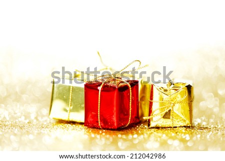 Decorative red and gold boxes with holiday gifts on shiny glitter background