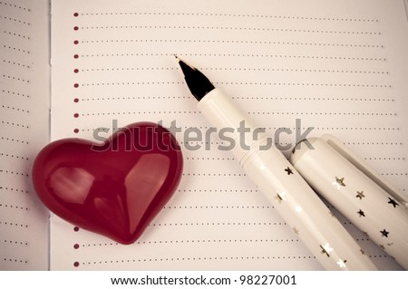 Decorative red heart and fountain pen on the blank page of notebook - stock photo