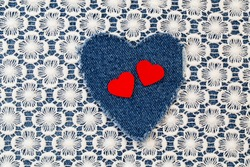 Decorative red heart and ripped denim  heart  frame on white lace background. Destroyed torn denim blue jeans frayed flap patch fabric.