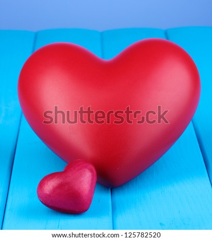 Decorative red hearts on blue wooden table on blue background