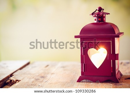 Decorative red metal lantern with a heart cutout lit by a glowing candle with copyspace for Valentines or Christmas #109330286