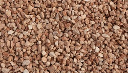 Decorative red pebbles used in garden or backyard around the plants. Background and texture