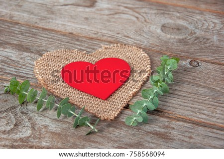 Decorative red wooden heart on on a burlap napkin in the shape of a heart a wooden background.Two Valentine hearts. Valentine's Day or Love concept.  #758568094