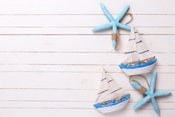Decorative sailing boats and marine items on wooden background. Sea objects on wooden planks. Selective focus. Place for text.
