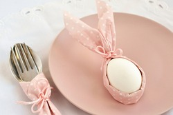 Decorative serving  of Easter table. A white egg with rabbit ears from a pink napkin on a plate with a spoon and fork.