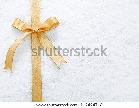 Decorative simple gold ribbon and bow on a background of winter snow with copyspace for your Christmas or festive greeting