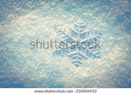 Decorative snowflake on the snow background, toned photo