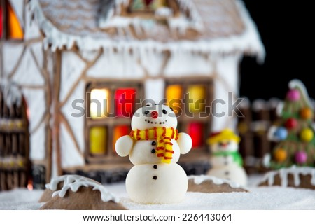 Decorative snowmen and gingerbread house with lights inside on black background. Rural Christmas night scene