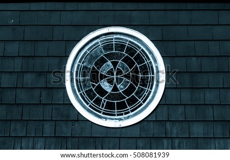 Decorative stained glass round window. Isolated stained glass circle window, Wood shingle siding with round window frame. Abstract art and design. Abstract colors and design. Architecture design.