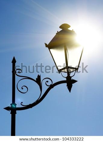 Decorative street lantern on blue sky background.