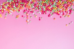 Decorative sugar sprinkles on a pink backdrop. Festive background for Birthday, holiday, party