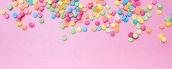 Decorative sugar sprinkles on a pink backdrop. Festive background for Birthday, holiday, party. Banner format
