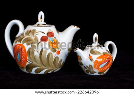Decorative tea pots  on black velvet texture background. Tea time. Colorful lifestyle. Modern stylish design