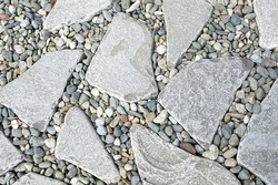 Decorative Tiled Footpath from Natural Stones Tiles. Tiled Walkway from Natural Stone Slabs and Marble Gravel. Garden Pathway from Natural Stones. Stony Tiled Background or Texture.