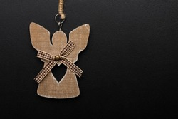 Decorative toy made of wood, Christmas angel with a heart on a black background. A clean space for your text. Copy space