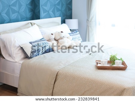Decorative tray with teddy bear, tea set and flower on the bed
