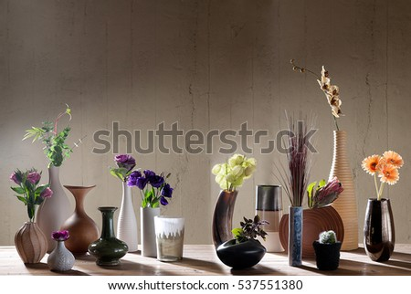 decorative vases and flowers with interior decor concept and wooden table