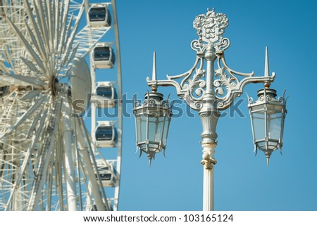 decorative victorian street lamp with ferris wheel in the background
