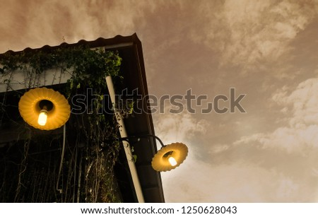 Decorative Vintage Lamp on The Roof Against Sunset Sky, Used to Illuminate Surrounding Space for Decorations and Atmosphere. #1250628043