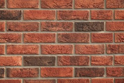 Decorative wall texture, background. Rusty, matted, red bricks. The fragment of a new stylish decorative bricklaying. Vintage and antique style in exterior of the house