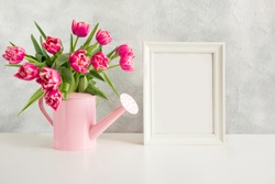 Decorative watering can with pink tulips and white photo frame for text. Gardening concept. Spring.