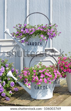 Decorative watering cans with flowers and text Garden
