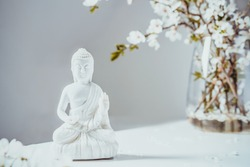 Decorative white Buddha statuette with blooming tree branches in the vase on the white background. Meditation and relaxation ritual. Buddha birthday. Selective focus