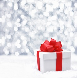 Decorative white gift box with a large red bow standing in fresh snow against a background bokeh of twinkling party lights