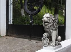 Decorative white stone lion statue near forged gates of a garden
