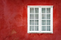 Decorative white window on an old red stucco wall