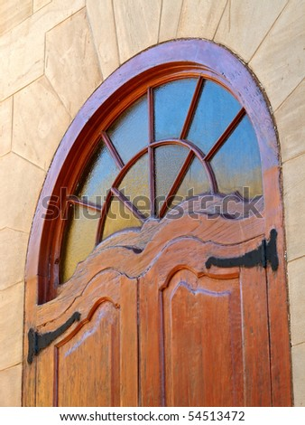 Decorative window in a wooden frame with sandstone walls