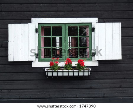 Decorative window of wooden cabin. Old wooden house in Norway. Decorative window with flowers.