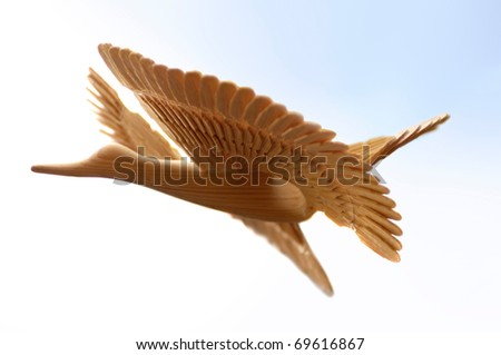 Decorative wooden bird Isolated over sky background