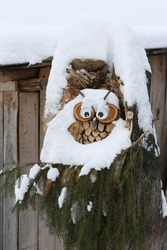 Decorative wooden owl and winter nature in Russia. Snow, snowy russian winter. Rural house. Rural life, winter in russian village. Snowfall, cold season in Sudislavl town, Kostroma region, Russia