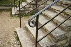 Decorative wrought iron handrail on external stone stairs (Marche, Italy, Europe)