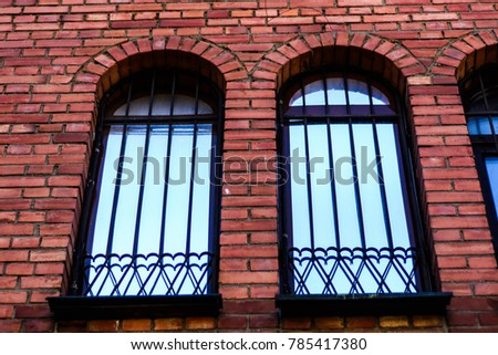 Decorative Wrought Metal Fence On The Windows Of Gothic Brick House