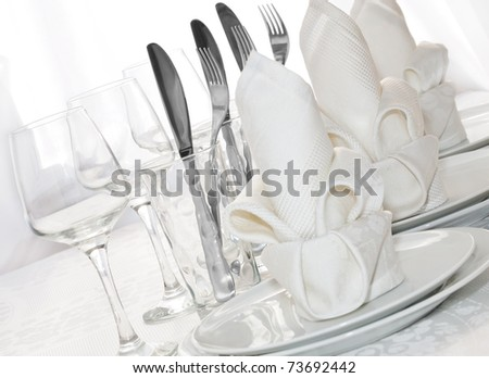 Decoratively folded napkins with glasses, glasses and cutlery