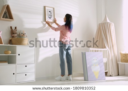 Decorator hanging picture on wall. Children's room interior design Foto stock ©