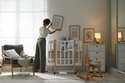 Decorator hanging picture on wall in baby room. Interior design