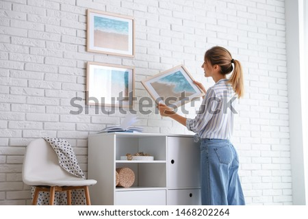 Decorator hanging picture on white brick wall in room. Interior design Foto stock ©