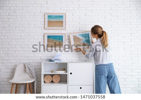 Decorator hanging picture on white brick wall in room. Interior design Photo stock ©