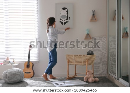 Decorator hanging picture on white wall in baby room. Interior design Foto stock ©