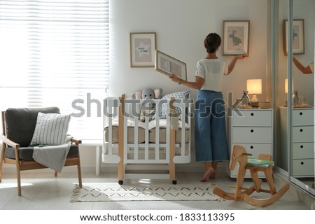 Decorator hanging pictures on wall in baby room. Interior design Foto stock ©