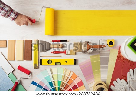 Shutterstock Decorator holding a painting roller and painting a wooden surface, work tools and swatches at bottom, banner with copy space